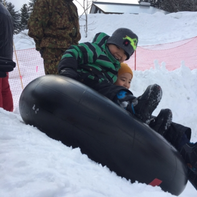 Having A Blast Riding Down On The Snow In A Winter Inner Tube